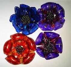 Soda Bottle Flowers.  Bake bottle bottom @ 200 for 10 minutes- need good ventilation.  Will shrink to 3/4 it's size.  When cool, color w/ permanent markers.  Glue small beads to center.