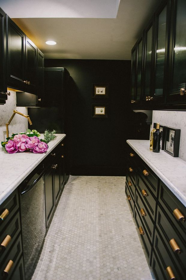 Kitchen with mosaic tile floor, brass hardware, marble counter tops, black cabinets. Design by Meredith Heron