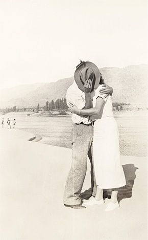 Young Russian American Eldred stands on Pacific Northwest riverbank kissing thirties sweetheart behind fedora held in right hand with left arm pulling her close. 1930s vernacular photo snapshot-www.reservatory.net
