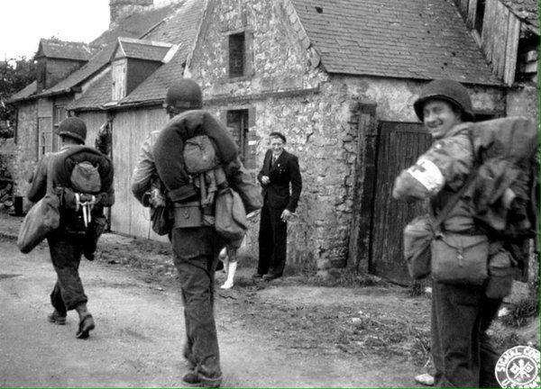 9th Infantry Division men pass through Sainte-Marie-du-Mont, Normandy, 6/11/44. http://awartobewon.com