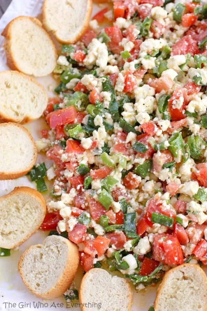 Easy feta dip - olive oil, tomatoes, onions, feta, & greek seasoning. Then serve with fresh baguette! I need to throw a party for how many good recipes I find on Pinterest