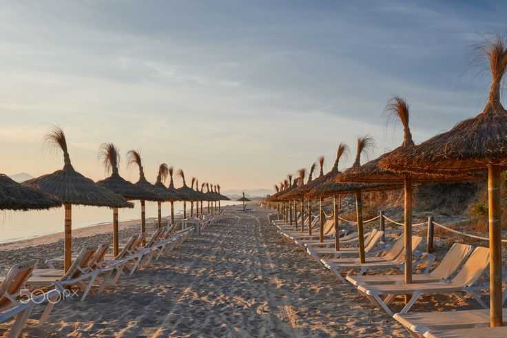 Sunrise on a resort beach with umbrellas - Sunrise on a deserted tropical resort beach with thatched umbrellas and recliner chairs overlooking a calm ocean for an idyllic summer vacation