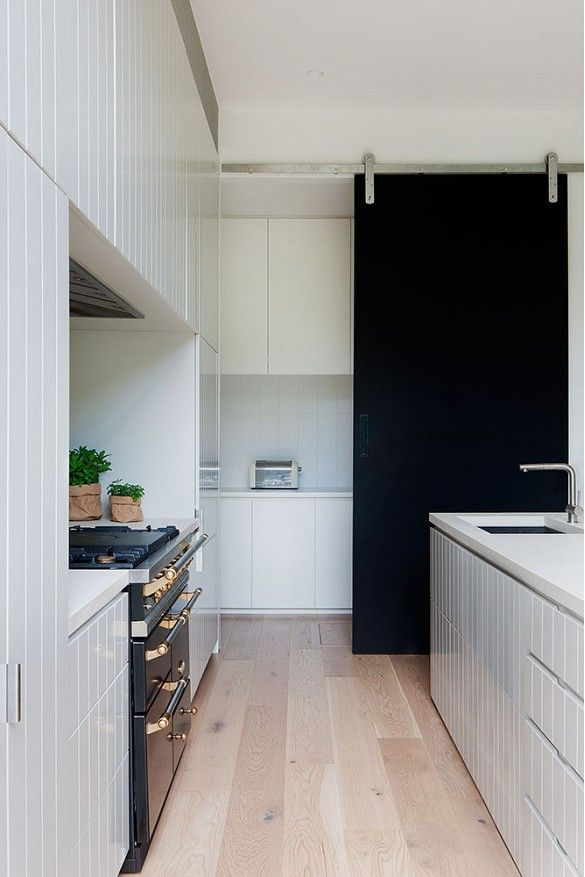 Black and white kitchen with black barn door