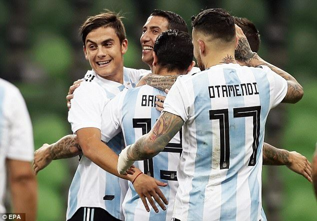 Ever Banega is mobbed by his Argentina team-mates after scoring the opening goal