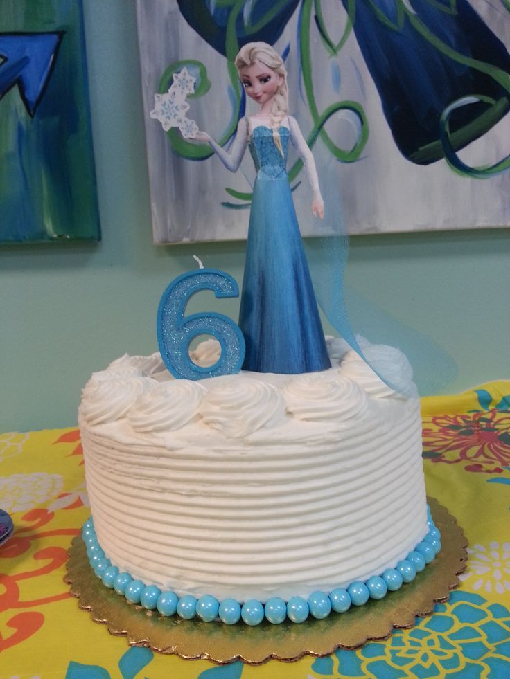 "Easy ""Frozen"" Cake - costs less than $20: Grocery store cake - Ask decorator to comb icing on sides and do swirlies around top; ask for no piping along bottom. Ice-blue Sixlets are in the cake decorator section of most stores - place along bottom. Print out Elsa Papercraft from Spoonful.com and assemble."