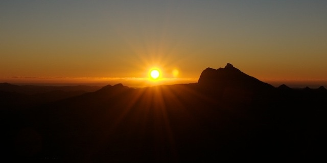 The sun rising behind Wollumbin. Photographed from the Border Ranges