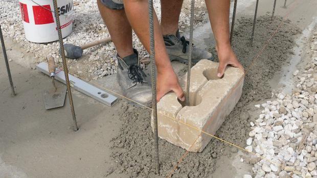 Setzen des ersten Betonsteines der Gartenmauer