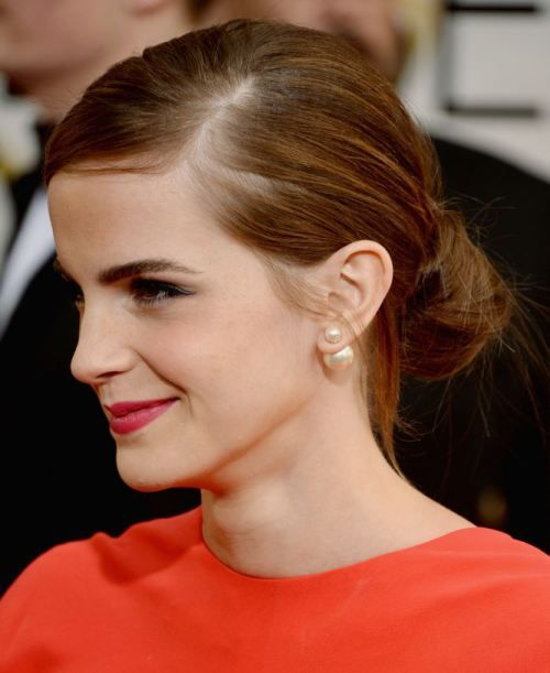 Emma Watson's messy knot belongs to those chic hairstyles you can effortlessly do yourself. You would divide your hair with a deep side parting, apply some foam to your locks and comb them back to make a tight pony at the nape. Twist the locks in your pony and wrap them around the elastic that holds them together. Fix the knot with bobby pins.