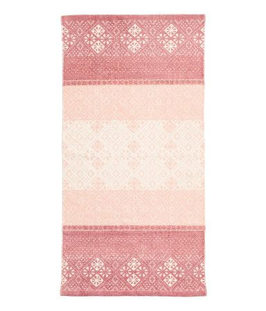 Light pink/dusky pink. Rectangular rug in woven cotton fabric with a printed pattern at front.