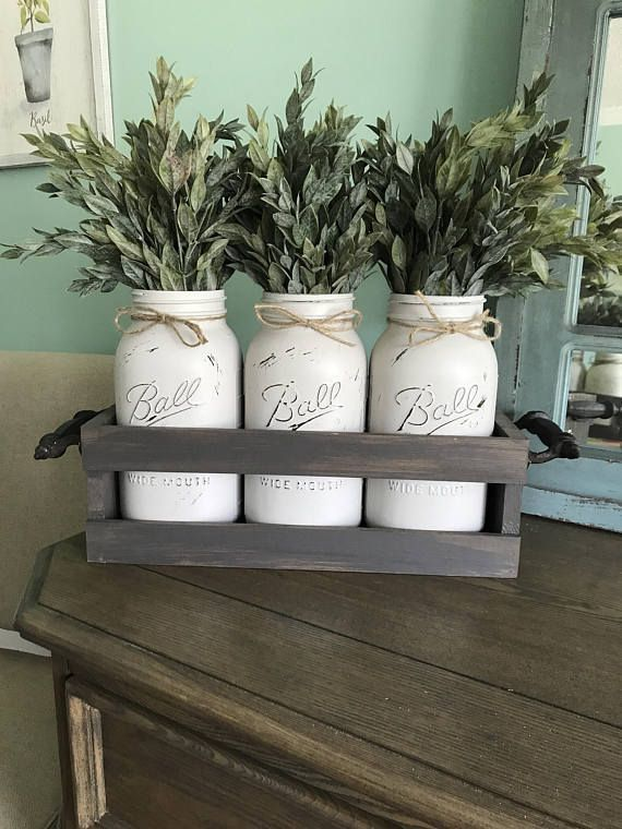 Looking for a farmhouse piece of decor that can go on your dining room table, mantle, or be given as a perfect gift? This is it! This includes a rustic crate with distressed wrought iron handles, three half gallon distressed gray jars, and beautiful greenery.