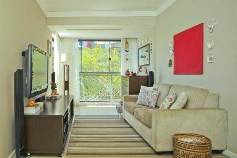 A moradora trouxe cor ao sofá ao combinar almofadas variadas sobre ele. As capas com estampa floral foram feitas de tricoline. O revisteiro é de palha de buriti trançada e para liberar espaço no tampo do rack, a TV foi fixada diretamente na parede.
