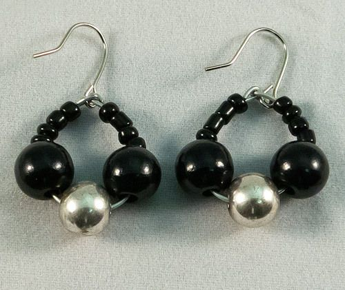 These are beautiful circular earrings made of a mix of black and metallic beads. The earrings measure at 2 cm.