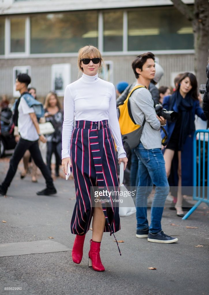 Lisa Aiken wearing striped skirt, white bag, red ankle boots is seen outside Loewe during Paris Fashion Week Spring/Summer 2018 on September 29, 2017 in Paris, France.