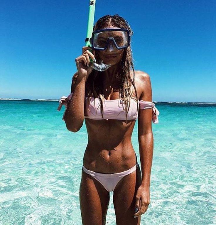 Back of a girl in a bikini with sunscreen