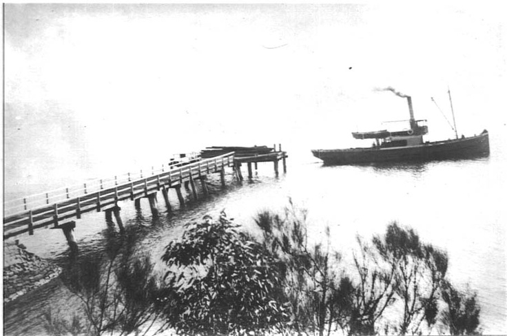 Cargo boat leaves timber at the wharf, 1920s.  Y. Emery