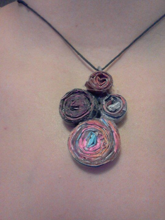 A Recycled necklace I made.  Take pages out of magazines with colors you want, accordion fold the pages then roll them up using a hot glue gun to secure the roll. Then take some cardboard (I used a cereal box) and glue the rolls to the cardboard (cutting around the edges then use a black permanent marker to color the back) Take some wire or I used a bread tie run it under the first roll and create a loop (hot glue to secrure), tie some stirng through it and VIOLA!