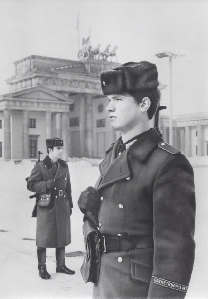 """East German Border Guards. Notice the cuff title, """"Grenztruppen der DDR"""", which means, """"Border Troops of the GDR"""" in English."""