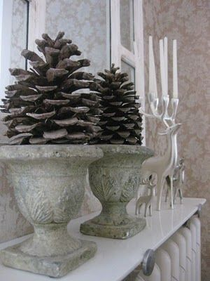 white mantle, large planters, large pinecones, silver reindeer with taper candles