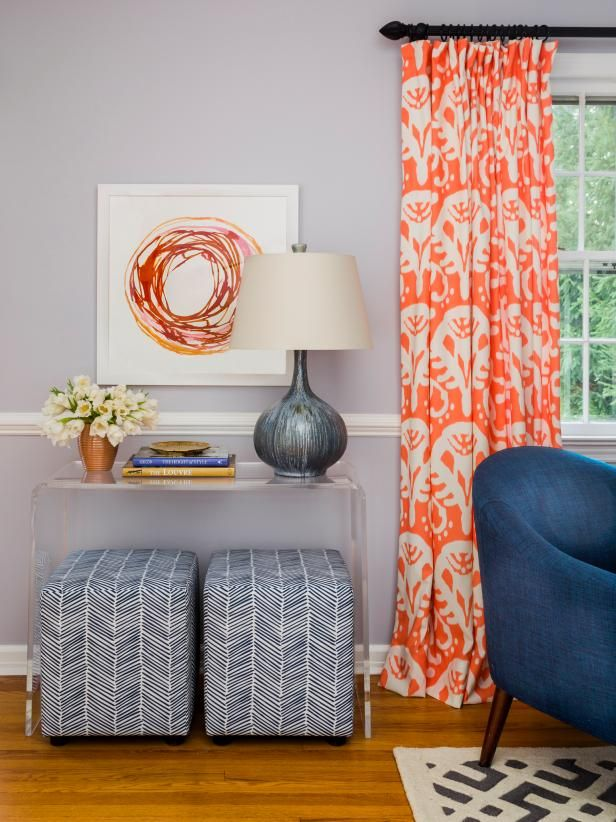 Reupholstered ottomans fit nicely under this clear console table. #hgtvmagazine http://www.hgtv.com/design/rooms/living-and-dining-rooms/make-your-living-room-look-20-years-younger?soc=pinterest