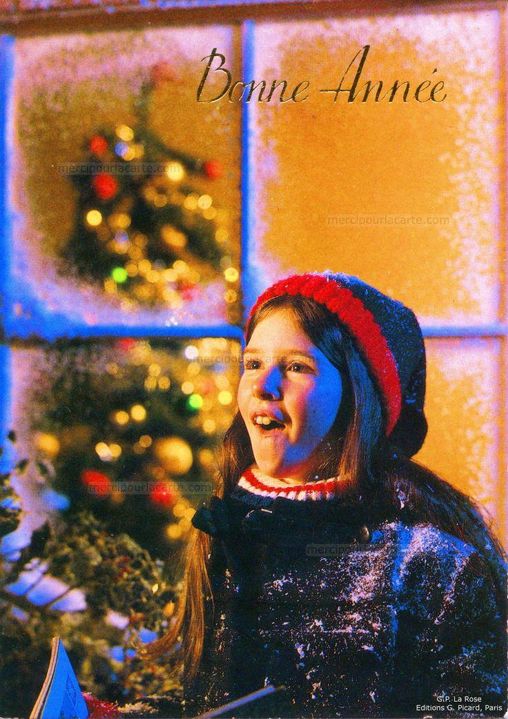 Bonne Année - Une fille emmitouflée en admiration, derrière la fenêtre givrée un sapin de Noël (from http://mercipourlacarte.com/picture?/1414/)