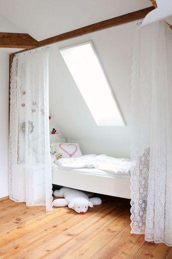 Bett unter der Dachschräge. Mit Vorhang leicht ab…
