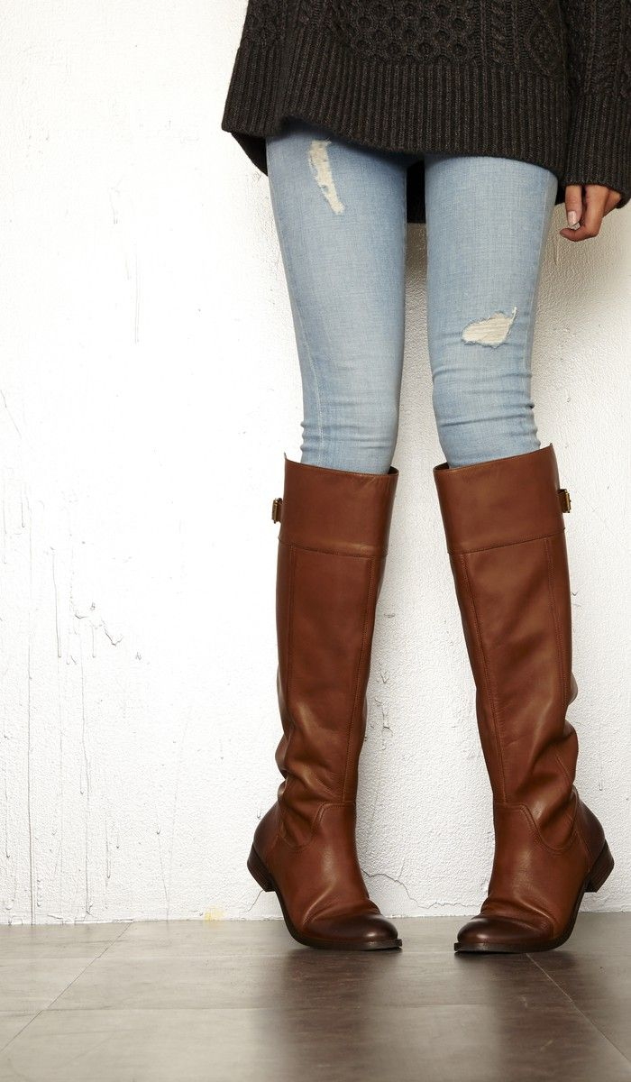 Luxurious leather riding boot with a back buckle detail and rounded toe. Note: Brown leather has distressed touches at toe and heel.