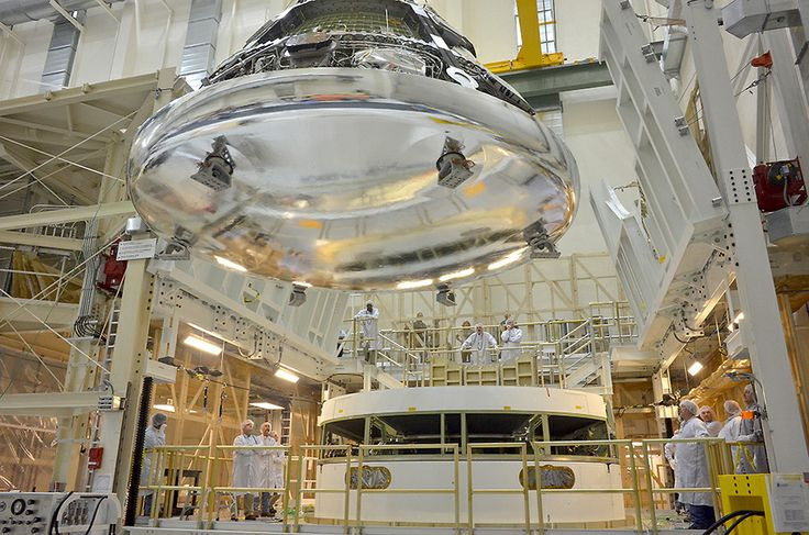 The Orion crew module for Exploration Flight Test-1 is shown in the Final Assembly and System Testing (FAST) Cell, positioned over the service module just prior to mating the two sections together. The FAST cell is where the integrated crew and service modules are put through their final system tests prior to rolling out of the Operations and Checkout Building at NASA's Kennedy Space Center in Florida.