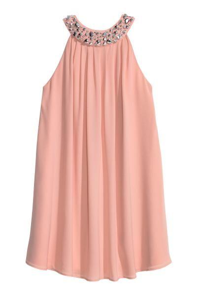 Vestido corto de tela con strass y pliegues en el cuello de estilo halter. Elástico y pliegues en la espalda, botones de presión ocultos en la nuca y cremal