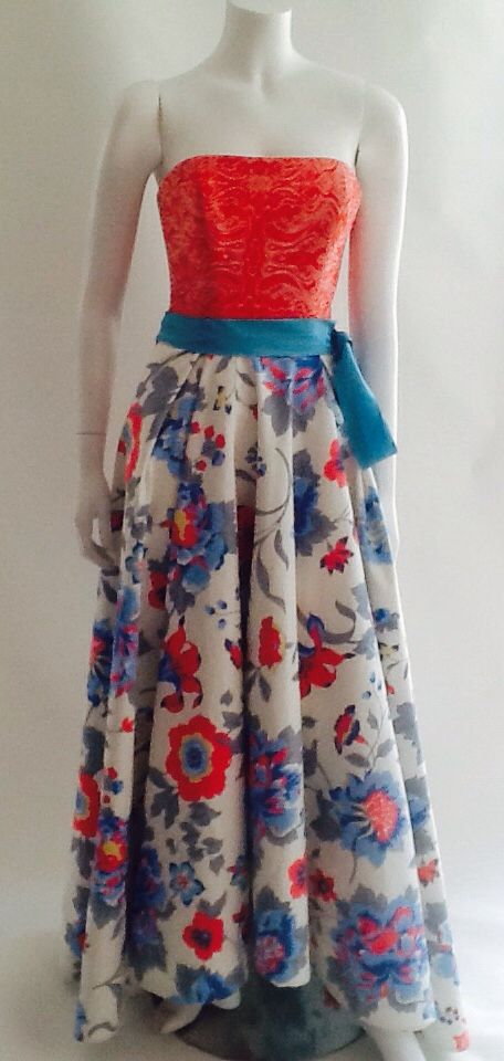 Cuerpo en gobelino strech, falda asimétrica en brocado floral de gabardina strech, complemento de cinturón tono azul cielo en tafeta de seda.