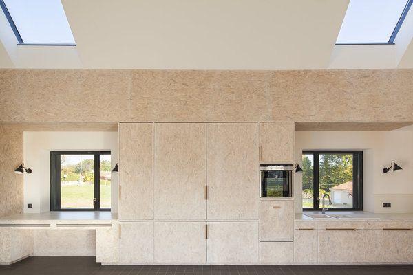 La vaste pièce à vivre a été habillée d'une cuisine sur mesure qui recouvre tout un mur. Deux puits de lumière, l'un au-dessus du plan de travail de la cuisine, l'autre au-dessus du bureau, viennent compléter l'éclairage latéral.