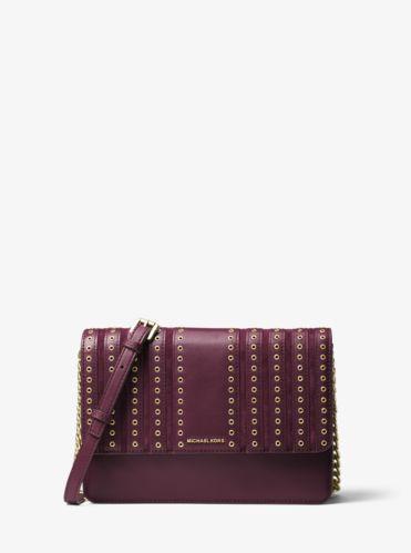 Le sac à bandoulière Brooklyn et ses œillets glamour s'inspirent de l'esprit bohème. L'alliance cuir/daim ajoute un riche plaisir tactile à ce modèle épuré, tandis que le logo de la marque crée une note raffinée de glamour emblématique.
