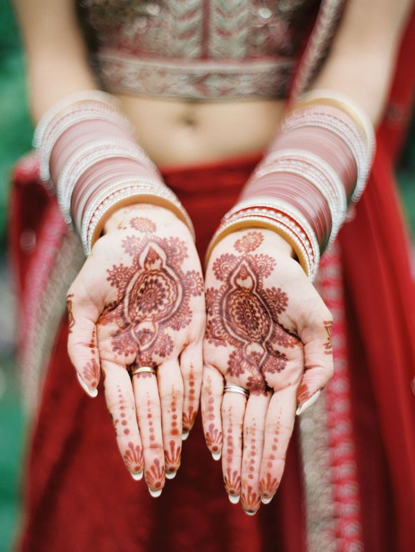 13 Wedding Details With International Flair | Bridal mehndi is an ancient custom that involves painting decorative henna on the bride-to-be. Although different variations and designs exist around the world, it's traditionally followed by a ceremony in Indian weddings.