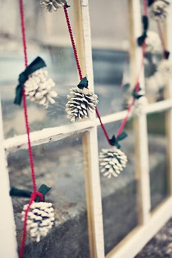 Painted white pinecones strung on red ribbon.