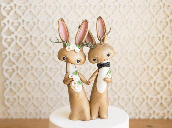 Ce souvenir Jackalope gâteaux de mariage dispose d'un Jackalope mariée et le marié. Je les sculpté à la main avec un mélange personnalisé composé polymère qui a un éclat subtil et persillage. Leurs bois délicats ont une patine et sont en étain, donc ils ne sont pas aussi délicats que leur apparence. Leurs yeux est en verre et ils se tiennent juste sous 6 pouces haut.  Vous recevrez la même paire exacte qui est dans les photos, et ils sont prêt-à-partir. Ils vont être sur leur chemin dans les…