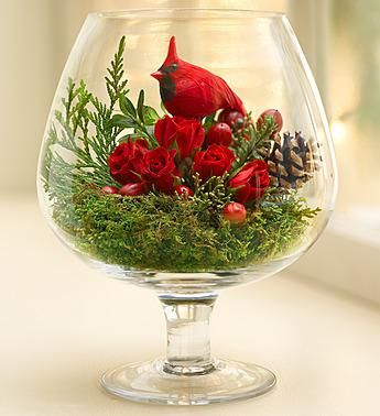 Soak oasis and place in a container. Cover with moss. Tuck tin roses, pine cones and greens. Add a little bird and you have instant charm for your table.