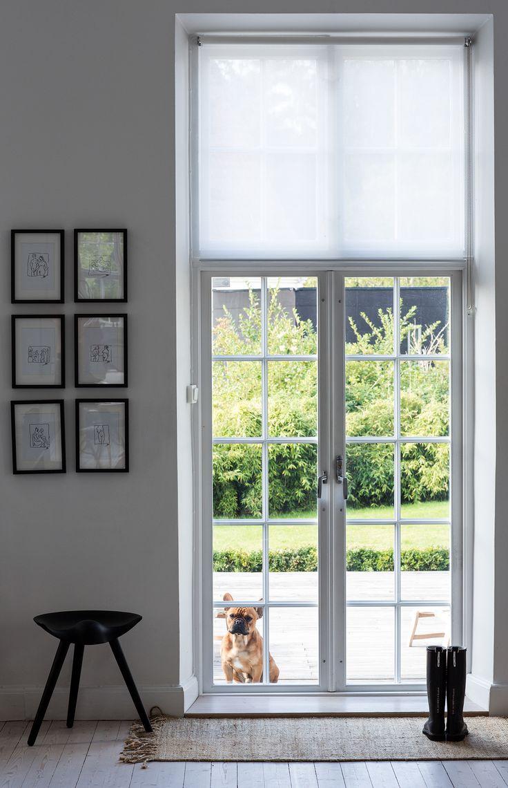 Vardagsrummets glasdörrar med vacker spröjs bjuder in till trädgården. Till vänster hänger Pias små konstverk och den trebenta pallen kommer från By Lassen.