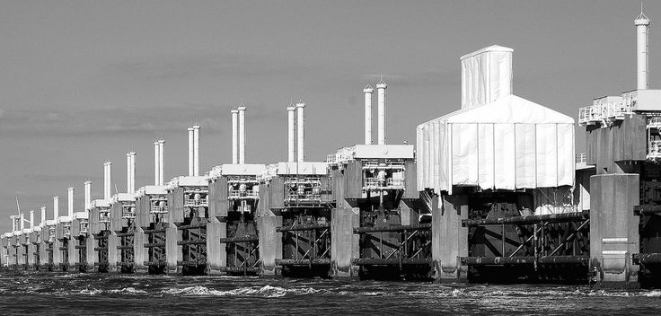 The Oosterscheldekering (Eastern Scheldt storm surge barrier), between the islands Schouwen-Duiveland and Noord-Beveland, is the largest of the 13 ambitious Delta works series of dams, designed to protect the Netherlands from flooding. The construction of the Delta Works was in response to the North Sea Flood of 1953.
