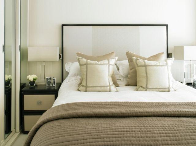 une tête de lit blanche et un linge de lit beige dans la chambre à coucher