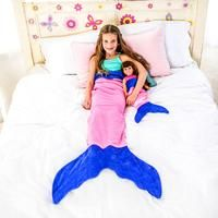 Girl on a bed in a Pink Mermaid Tail Blanket with her doll