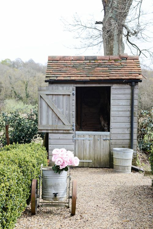 Pretty shed. Could be made from reclaimed wood and roof tiles.