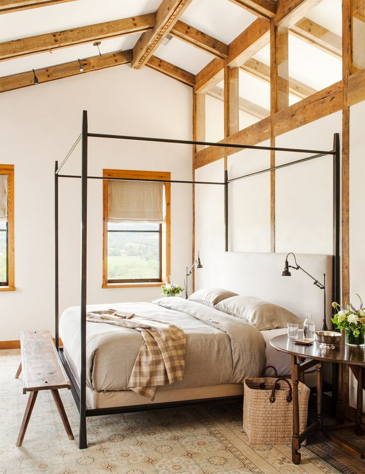 Black bed frame, taupe bed sheets, wood bench, and wood night stand