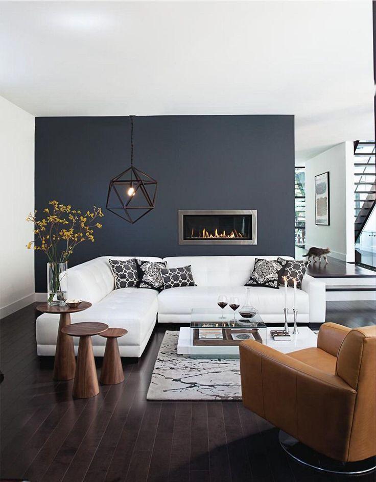 Soggiorno di ispirazione scandinava, moderno ed elegante, con un bel contrasto bianco e nero - camino a bioetanolo inserito nel muro, divani in pelle e pavimenti in legno