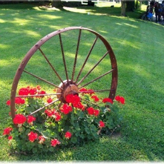 Wagon wheel. Ive seen these at Garden Ridge. Maybe I could doe something like this near the fence or driveway.
