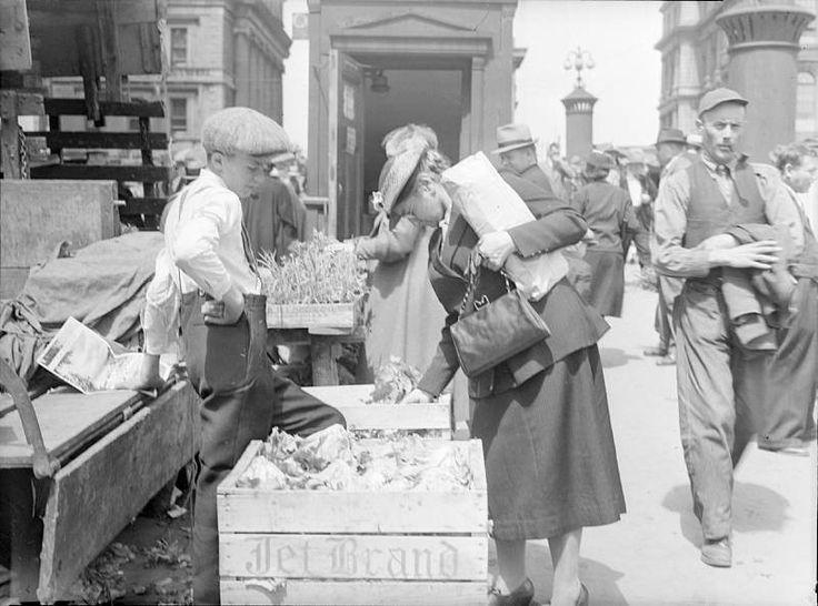 Un gamin vend des laitues à une cliente sur la place du marché Bonsecours. Photo de Conrad Poirier, 1940 (Source BAnQ).