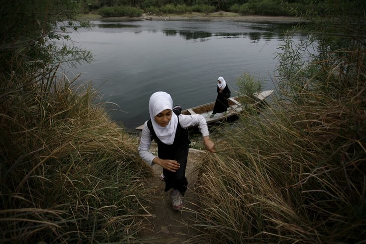An Iraqi school girl walks up the bank of a river after crossing the waterway on a small wooden boat in the district of Al-Mishikhab, some 25 kilometers south of the holy city of Najaf, as they head to school on April 1, 2015. According to Iraqi women in this area boat is one of the only ways for them to travel.