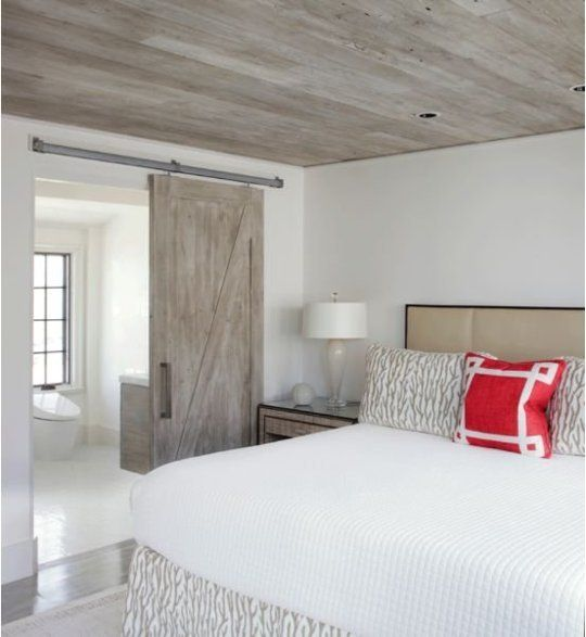 A modern version of the look is seen in this Florida bedroom. Keeping the ceiling, barn door, and bathroom vanity the same material creates flow and serenity, while the rustic wood itself is a cool feature.