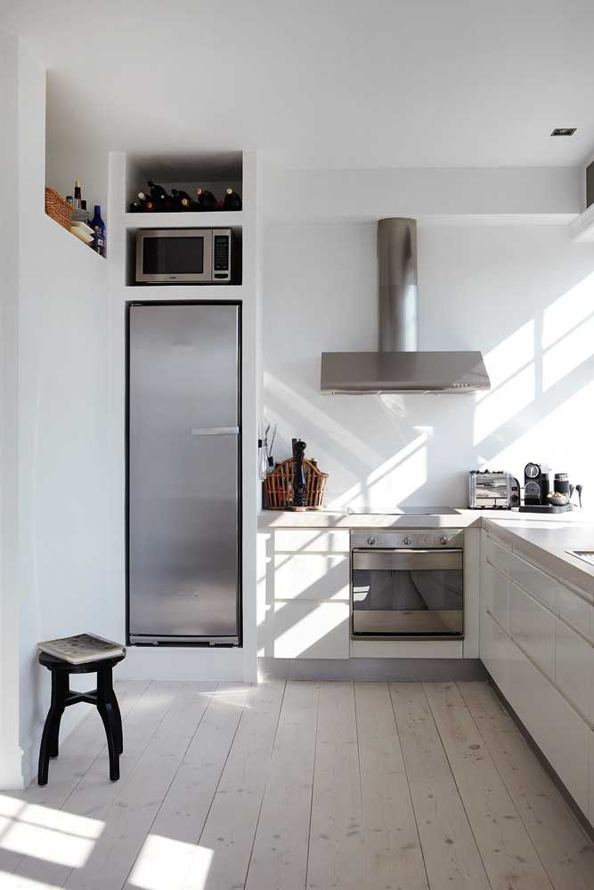 white, wood and stainless. swedish minimalist white kitchen with recessed storage areas. photo by kira brandt.