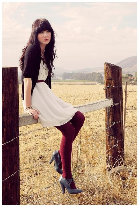 White dress, sweater, red tights, grey boots. sitting on a barbed wire and wodden fence