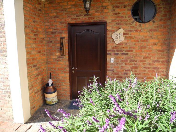 Una entrada entre jardines y pajaros son el toque de la cabaña agua