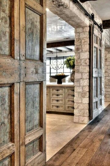 Love the rock, time and stone, along with the distressed wood kitchen cabinets. Those rustic barn doors take the cake though!
